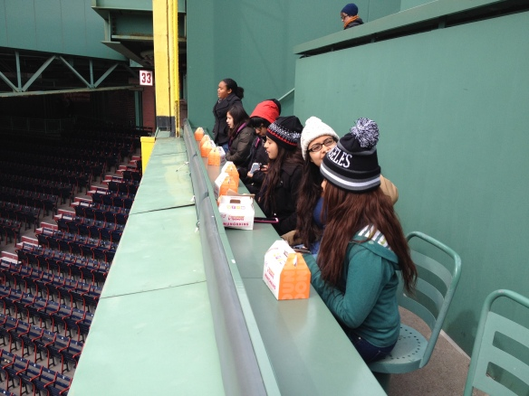 Sitting on the Green Monster with Dunkin' Donuts swag.