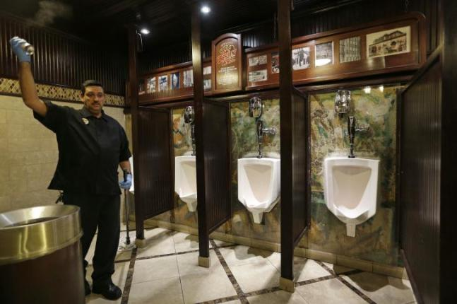 Julio Fernandez sprays air freshener while mopping up a mess in a bathroom at the Main Street Station casino, Las Vegas. The wall holding up the urinals is a piece of the Berlin Wall. The wall that once separated East from West Berlin has largely disappeared from the city. The few sections that remain stand as potent monuments to the ideological divisions of the Cold War. But 25 years after the Berlin Wall fell, some 120 parts of it can now be found in more than 40 countries, from Britain to South Africa and the United States. (AP Photo/John Locher)